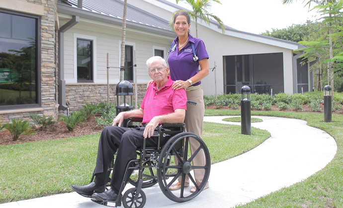 A man using a wheelchair on an outside path receives help from a VITAS team member