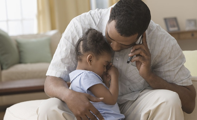 A man talks on the phone while holding his young daughter