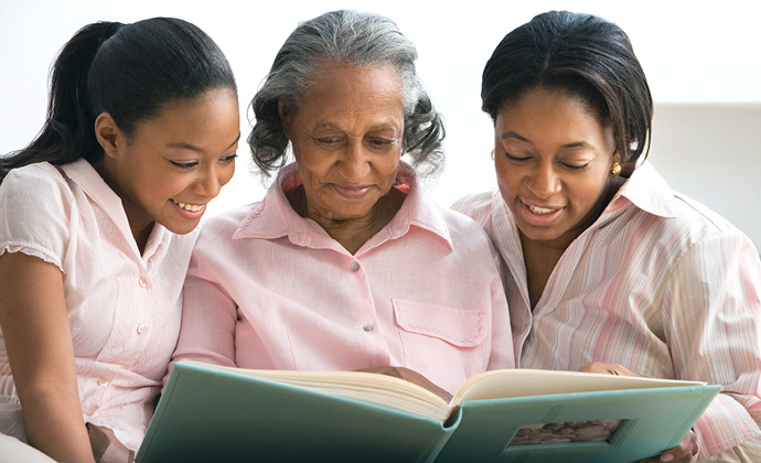 A woman looks at a family photo album with her two granddaughters