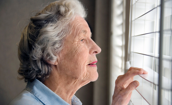 An older woman looks out a window