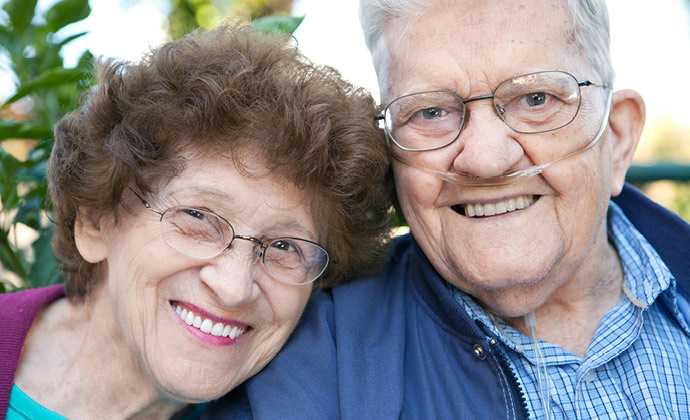 A man wearing oxygen tubes smiles next to his wife