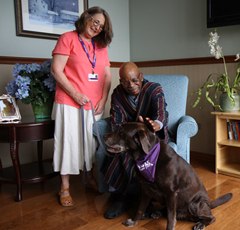 A Paw Pals volunteer brings a dog to comfort a patient