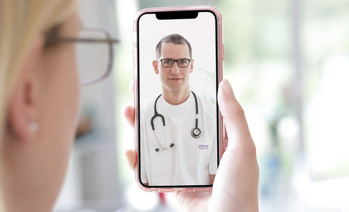 A woman talks with a physician on a videoconference via smartphone